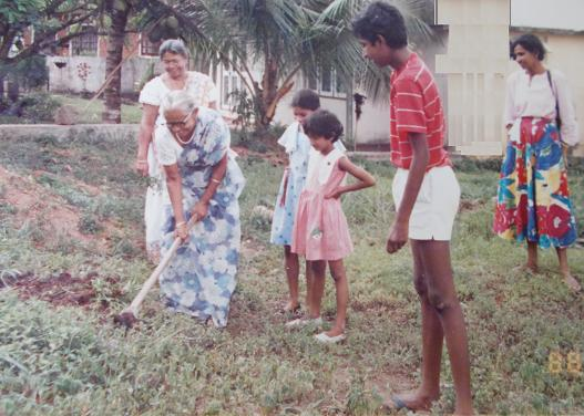 Before laying the foundation stone, @ 56, Siripura  The new plot of land, my parents bought, before we built a house. On my sister's 8th Birthday (20th October 1988) Our family came to live in SL, for good, in January 1988. We bought this land, built a house, and moved in, in January 1990. In this picture: we all took turns cleaning the land, before laying the foundation stone, on Sachi's 8th Birthday. Attammi is seen .. Behind her is Achchi (my paternal grandmother). Dressed in a blue frock, is the B'day girl. In a pink dress, a cousin of mine (my mother's niece). A lanky tall 13 year old me. And my mother (far right).